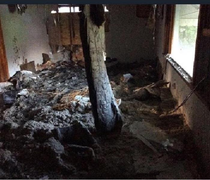 Drywall and insulation cover the ground in a living room after collapsing from the ceiling