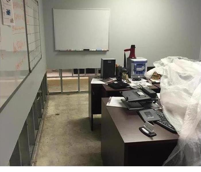 An office showing the drywall was removed 2 feet up from the floor