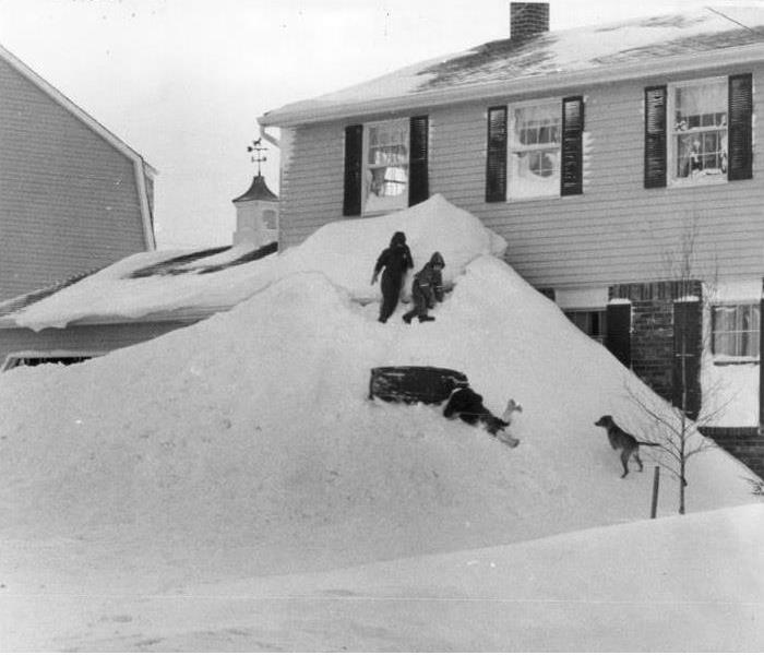 Snow buildup to the second story of a home. Kids sled down