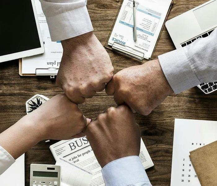 A team of business people bumping hands together