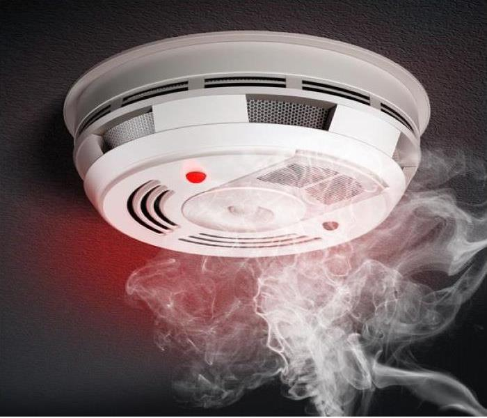 A smoke detector on the ceiling. Smoke rises towards it
