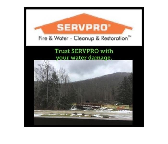 A photo of a scenic mountain and creek with the Servpro logo above it.