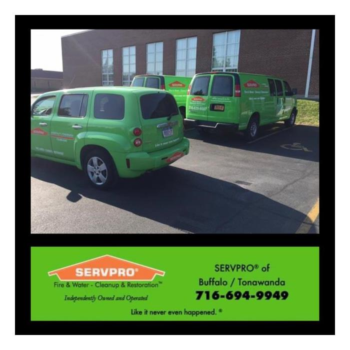 A photo showing three SERVPRO vans at a commercial water damage.