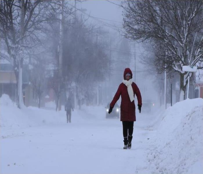 A woman walks on a street during a snowstorm