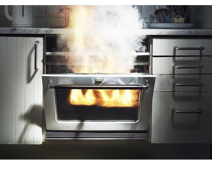 An oven door is open with an orange glow of flames and smoke coming out.